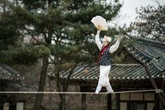 La acrobacia en una cuerda tirante que camina en el pueblo popular coreano Foto de archivo libre de regalías