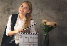 La actriz está sosteniendo la película de la pizarra y está expresando la emoción a los movimientos de la prueba foto de archivo libre de regalías