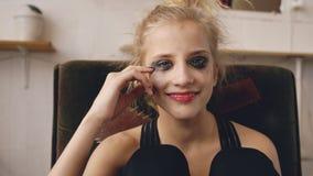 La actriz joven del adolescente con maquillaje manchado sonríe después de parada que llora debido al bastidor de la película de l Fotografía de archivo libre de regalías