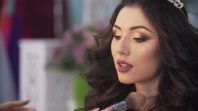 La actriz magnífica se está preparando para tirar El artista de maquillaje desconocido está aplicando maquillaje en la cara de la almacen de video