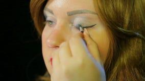 La actriz pelirroja en el vestuario hace maquillaje del ojo con las sombras de plata que se preparan para ir en etapa almacen de metraje de vídeo