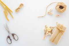La actual caja de regalo de DIY, hierba seca, una bobina de la cuerda y scissor aislado en una tabla blanca, materiales caseros d fotos de archivo libres de regalías