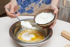 La adición de crema agria en la pasta Fotografía de archivo