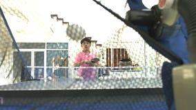 La adolescencia asiática del muchacho practica tenis de mesa de la máquina del ping-pong del robot,