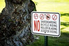 La advertencia del monopatín canta en un parque con el árbol Imagenes de archivo