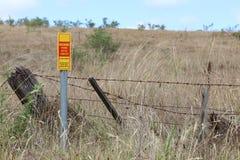 La advertencia roja y amarilla, los cables fibroópticos en esta vecindad firma Fotografía de archivo