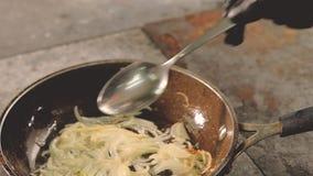 La agitaci?n del cocinero del cocinero de la comida cort? el ingrediente de la cacerola de las cebollas almacen de metraje de vídeo