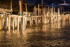 La agua de mar alcanza las sillas y las tablas que están en la orilla de la playa imagen de archivo libre de regalías