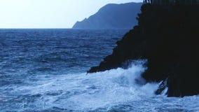 La agua de mar azul agita estrellarse en el acantilado rocoso que forma la espuma, clima tempestuoso almacen de metraje de vídeo