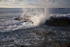 La agua de mar pega una roca en la orilla de mar imagenes de archivo