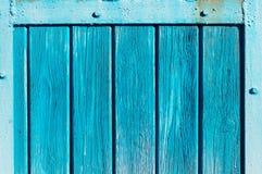 La aguamarina coloreó la puerta de madera con las rayas del hierro imagenes de archivo