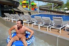 La aguamarina parquea la diversión - hombre joven que monta abajo de un tobogán acuático Imágenes de archivo libres de regalías