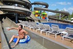 La aguamarina parquea la diversión - hombre joven que monta abajo de un tobogán acuático Foto de archivo libre de regalías