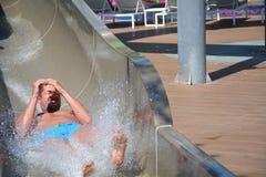 La aguamarina parquea la diversión - hombre joven que monta abajo de un tobogán acuático Imagen de archivo