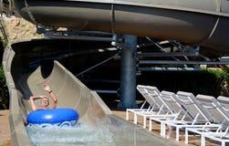 La aguamarina parquea la diversión - hombre joven que monta abajo de un tobogán acuático Imagen de archivo libre de regalías