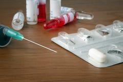 La aguja de la jeringuilla con un primer 2 de la píldora Imagenes de archivo