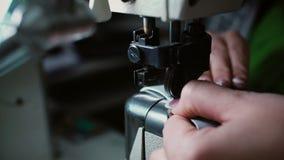 La aguja de la máquina de coser cose en una materia textil azul El trabajador cose el cuero para la producción del zapato 4K metrajes