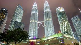 La alameda ligera de las torres gemelas KLCC de Petronas de la noche en el centro de la ciudad remata malaisia del lapso de tiemp almacen de metraje de vídeo