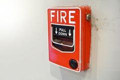 La alarma de incendio y el equipo roja en la pared blanca Fotografía de archivo