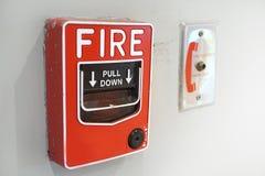 La alarma de incendio y el equipo roja en la pared blanca Imagen de archivo