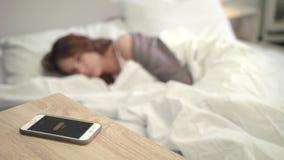 La alarma móvil despierta a la mujer en cama Despierte el tiempo por mañana Nuevo día femenino almacen de video