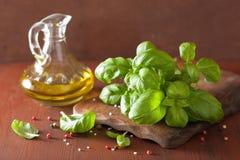 La albahaca fresca deja la hierba y el aceite de oliva en bacgkround de madera foto de archivo