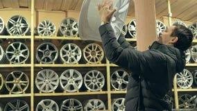 La aleación de las compras del hombre rueda adentro su tienda para su coche almacen de video