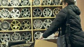 La aleación de las compras del hombre rueda adentro su tienda para su coche almacen de metraje de vídeo