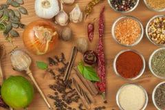 La alegría de cocinar, preparación de especias Diversas clases de especias en un tablero de madera Preparación de alimento Imágenes de archivo libres de regalías