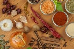 La alegría de cocinar, preparación de especias Diversas clases de especias en un tablero de madera Preparación de alimento Fotos de archivo