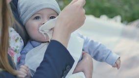 La alimentación de la madre un pequeño hijo con un yogur metrajes