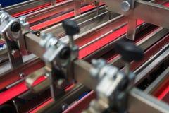 La alimentación roja plegable de las correas de la máquina rueda el dispositivo industrial del metal Imagen de archivo