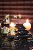 Flores de la almendra con las velas y las piedras negras Fotos de archivo libres de regalías