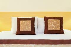 La almohada roja en dormitorio con la hoja de cama blanca y la lámpara se encienden encendido Foto de archivo