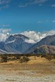 La alta nieve capsuló las montañas alrededor de la roca media de la tierra, Nueva Zelanda Imagen de archivo