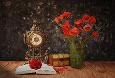La amapola florece en un florero con un libro Foto de archivo