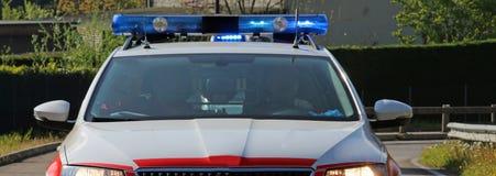 La ambulancia con las sirenas dio vuelta encendido corre rápidamente en el camino Foto de archivo libre de regalías