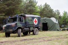 La ambulancia militar alemana se coloca en sistema del centro del rescate en una madera Imagen de archivo libre de regalías