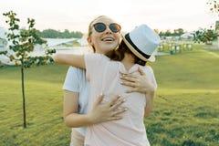 La amistad de dos adolescentes, las mejores novias se divierte en naturaleza, en el césped verde del parque y del entretenimiento foto de archivo libre de regalías