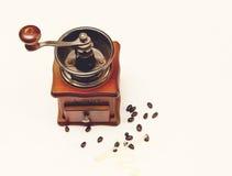La amoladora de café de madera del montante viejo del vintage con las habas de Coffe en el fondo blanco, visión superior Imágenes de archivo libres de regalías