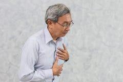 La anciano asiática sufre de dolor de pecho del ataque del corazón imagen de archivo