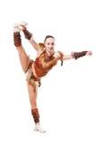 La animadora profesional joven se vistió en un traje del guerrero; colocación en una pierna Imagenes de archivo