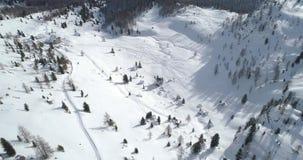 La antena delantera sobre el llano y el valle nevosos de la nieve con las pistas del esquí en Cinque Torri monta Día soleado con  almacen de metraje de vídeo