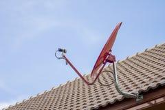 La antena parabólica roja en el tejado Fotografía de archivo libre de regalías