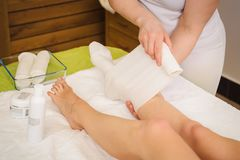 la Anti-cellulite avvolge la procedura per le gambe in un centro della stazione termale immagine stock