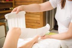 la Anti-cellulite avvolge la procedura per le gambe in un centro della stazione termale immagini stock libere da diritti