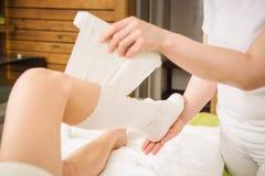 la Anti-cellulite avvolge la procedura per le gambe in un centro della stazione termale fotografia stock libera da diritti