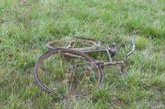 La antigüedad o la bicicleta oxidada retra se fue abajo en la hierba Fotos de archivo libres de regalías