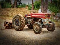 La antigüedad vieja de la moda llevada aherrumbró tractor de cuatro ruedas rojo rural entre árboles verdes Tractor de correa esla Foto de archivo