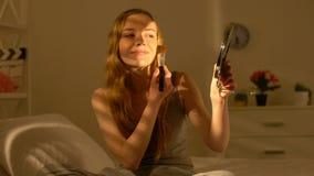La aplicaci?n atractiva sonriente de la hembra se ruboriza llevando a cabo la peque?a mano del espejo, maquillaje metrajes